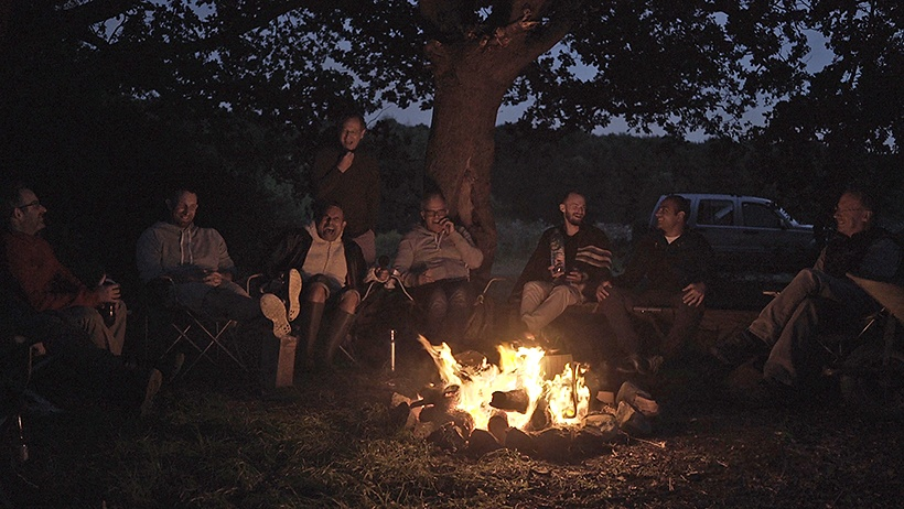 a men's group around a campfire